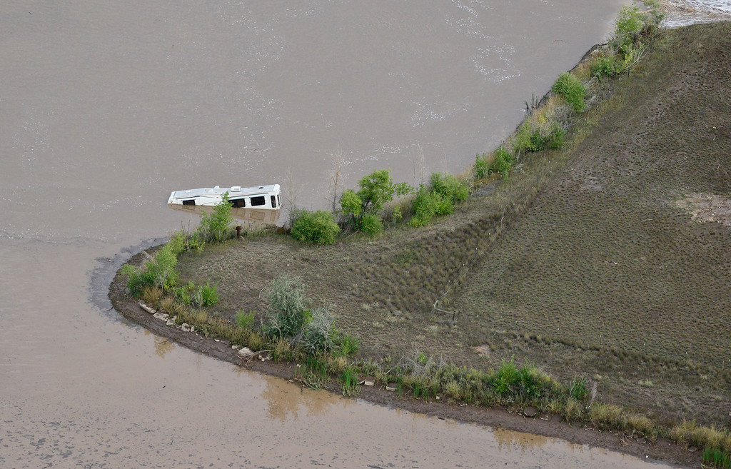 Description of . A partially submerged RV trailer is seen floating in a lake, Saturday, Sept. 14, 2013. (Matthew Jonas/Times-Call)
