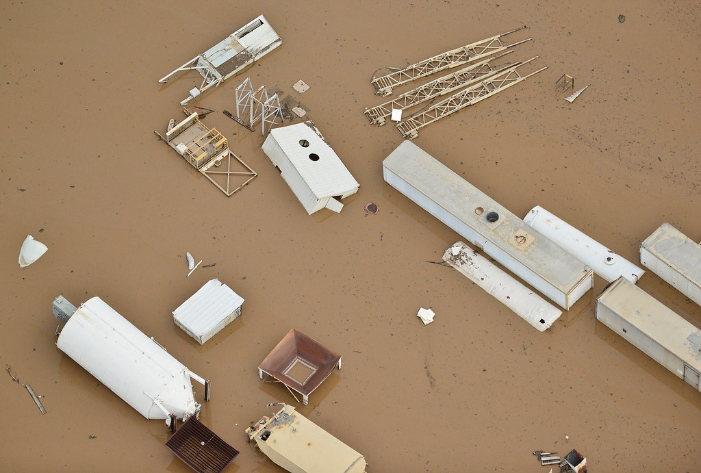 Description of . Storage tanks and buildings are seen floating in the flood water, Saturday, Sept. 14, 2013, near Longmont. (Matthew Jonas/Times-Call)