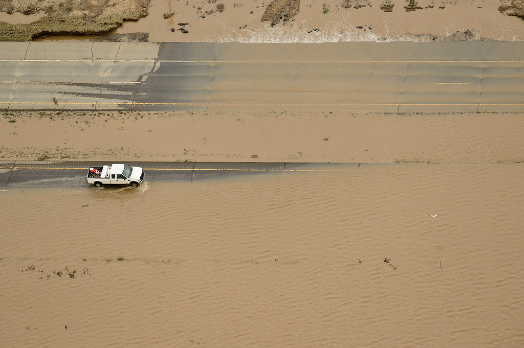 Description of . A truck drives through flood water on Highway 119 east of Longmont, Saturday, Sept. 14, 2013. (Matthew Jonas/Times-Call)