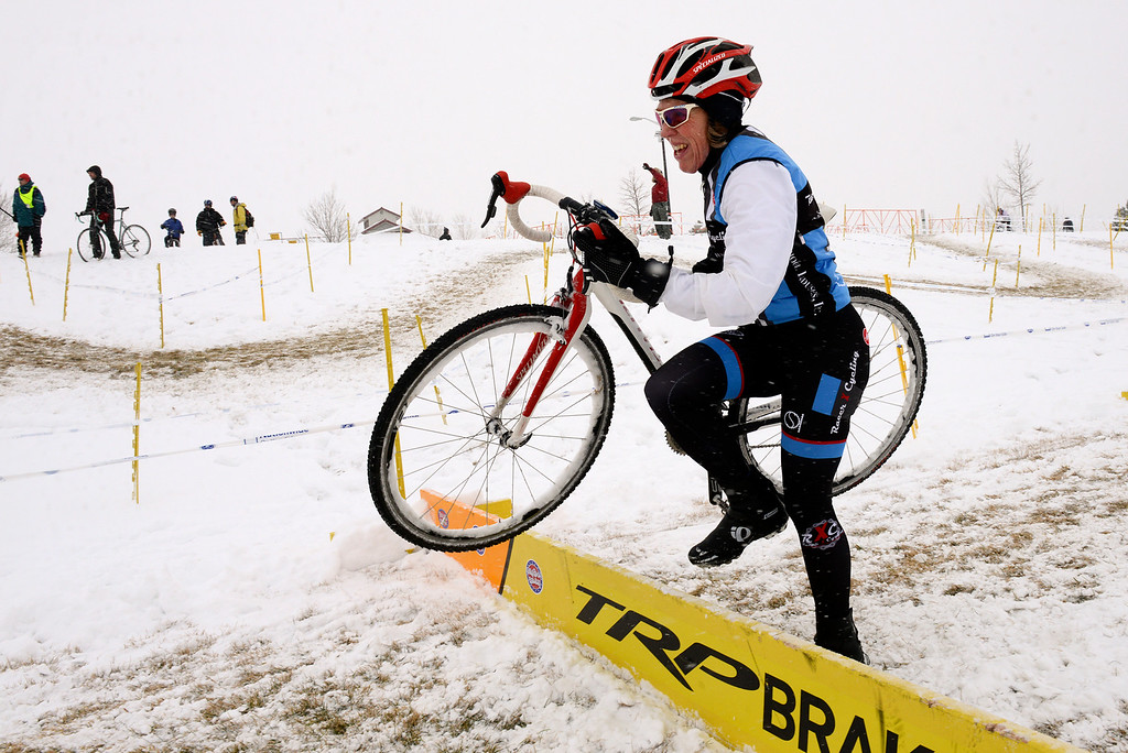 Description of . Maurine Sweeney, of Highlands Ranch, makes her way over a barrier Saturday, January 04, 2014 during the Altitude Adjustment Cross cyclocross race at Sandstone Ranch. (Lewis Geyer/Times-Call)