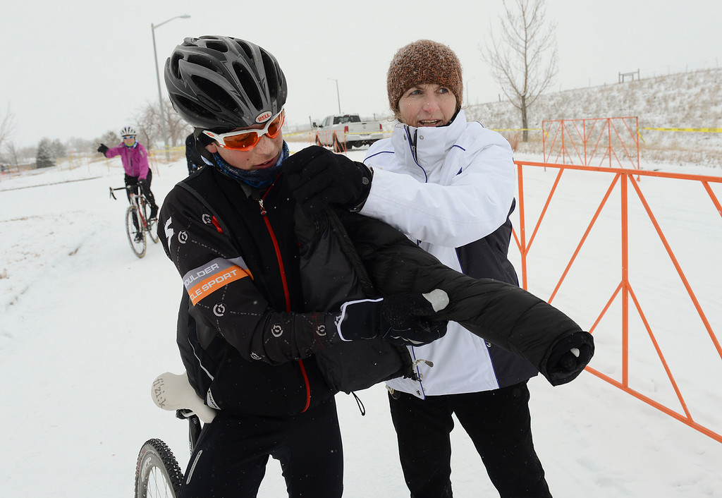 Description of . Nolan Stephenson, 12, of Broomfield, gets help with his jacket from his mother Rita Stephenson Saturday, January 04, 2014 after Nolan won his juniors' race during the Altitude Adjustment Cross cyclocross at Sandstone Ranch. (Lewis Geyer/Times-Call)