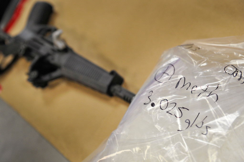 Description of . A bag containing 3.025 pounds of meth is seen next to a gun in evidence, Wednesday, Aug.  7, 2013, at the Longmont Police Department. (Matthew Jonas/Times-Call)