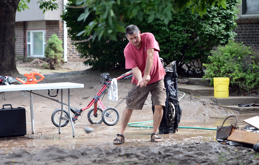 Description of . Jim Christofferson swings a golf club during a lighter moment while cleaning out the mud at his home on Lefthand Drive in Longmont, CO., on September 14, 2013.