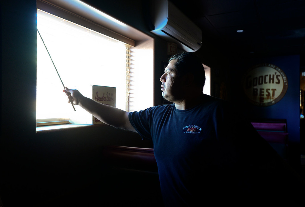 Description of . Smokin\' Daves BBQ and Taphouse Manager Luis Montes opens blinds to let light into the building while checking for damage, Wednesday, Sept. 18, 2013, in Lyons. All the utilities for the town of Lyons are currently down including, water, power and sewer service.