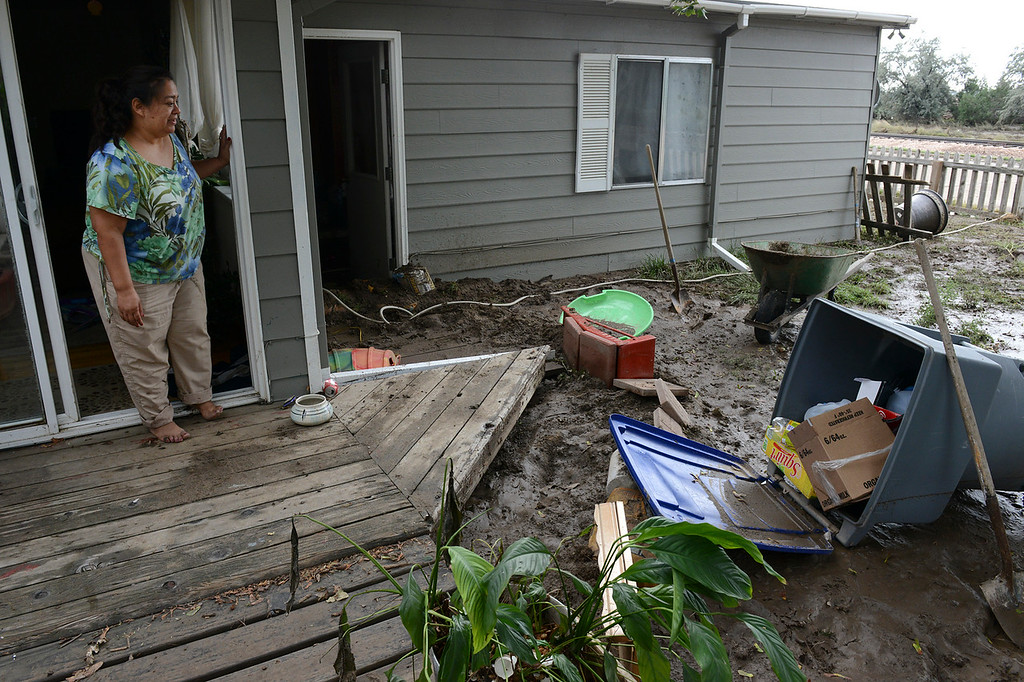 Description of . Rosa Garcia surveys the flood damage to her home at First Avenue and Elizabeth Court, in the Bohn Park neighborhood, Saturday morning, Sept. 14, 2013. Garcia, who has lived there for 15 years, said she has no flood insurance. (Lewis Geyer/Times-Call)
