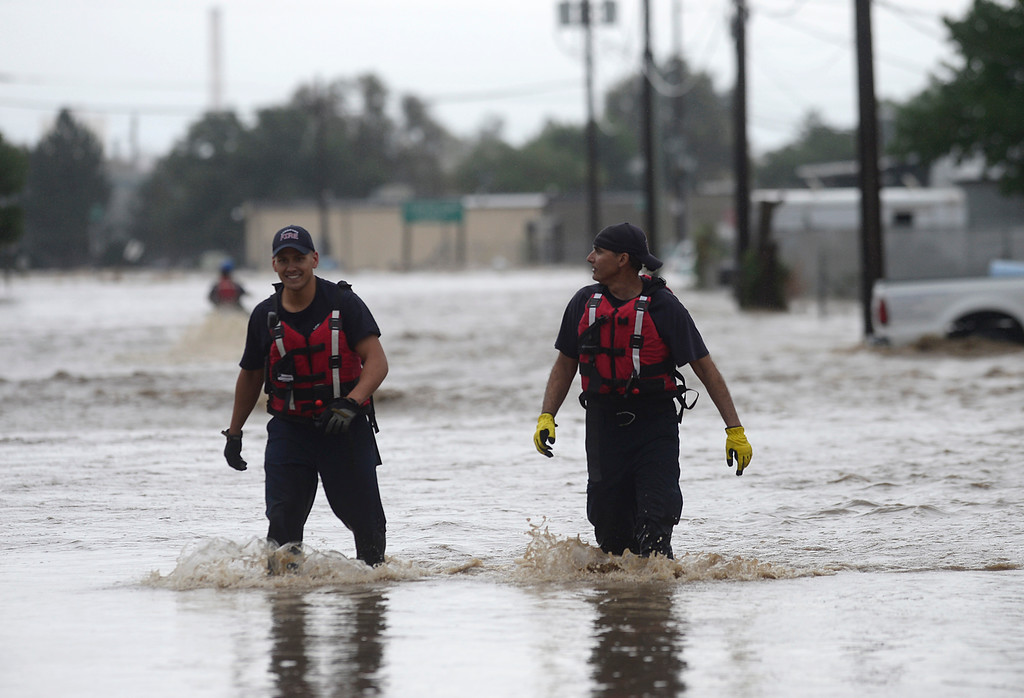 Description of . Longmont firefighters Ian Cofrin, left, and engineer Todd Feaster walk on a flooded Boston Avenue after helping launch a jet ski Thursday Sept. 12, 2013. (Lewis Geyer/Times-Call)