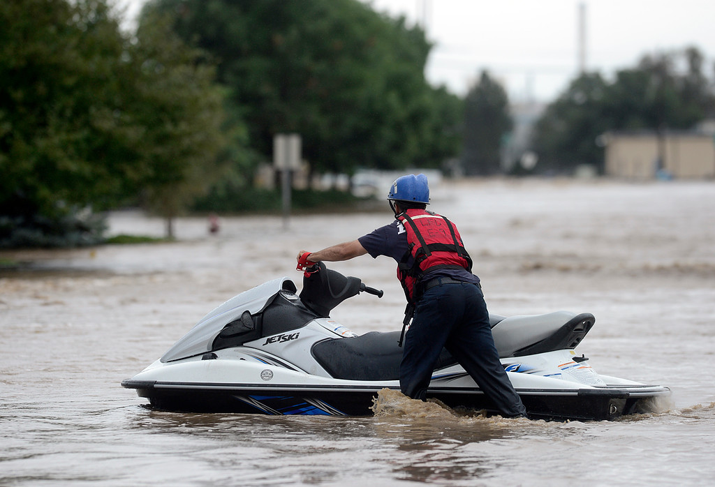 Description of . A Longmont firefighter uses a jet ski on Boston Avenue, near Left Hand Brewery, Thursday Sept. 12, 2013. (Lewis Geyer/Times-Call)