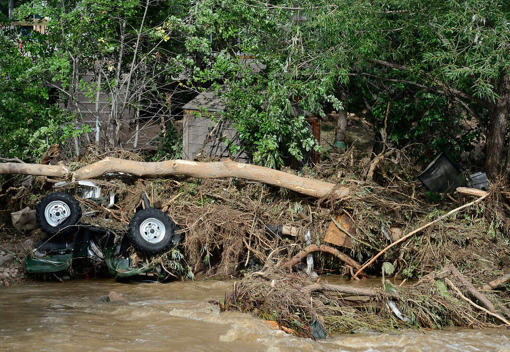 Description of . A damaged ATV and piles of debris are seen near the edge of St. Vrain River off 2nd Avenue, Monday, Sept. 16, 2013, in Lyons.