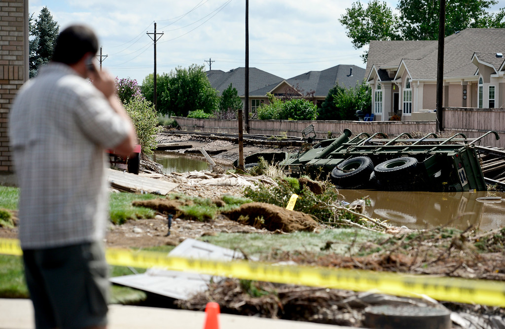 Description of . Adam Oser, of Johnstown, talks on the phone while looking at his submerged M-923 off Twin Peaks Circle, Monday, Sept. 16, 2013, in Longmont.