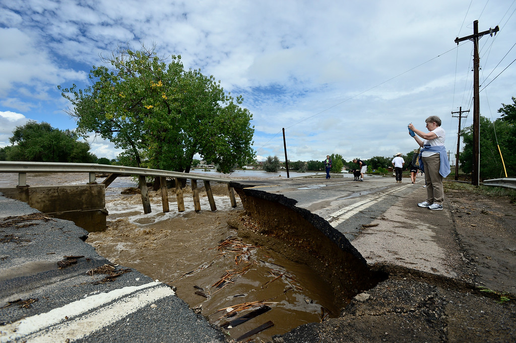 Description of . A woman takes photos of a guard rail and flood damage on County Line Road, Friday, Sept. 13, 2013, near Longmont.