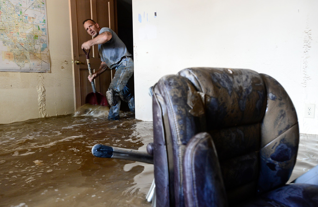 Description of . Robert Pandolfi, of Longmont, helps to push water to a pump while working in the basement of Ray Hummer (not pictured) on Twin Peaks Circle, Monday, Sept. 16, 2013, in Longmont.