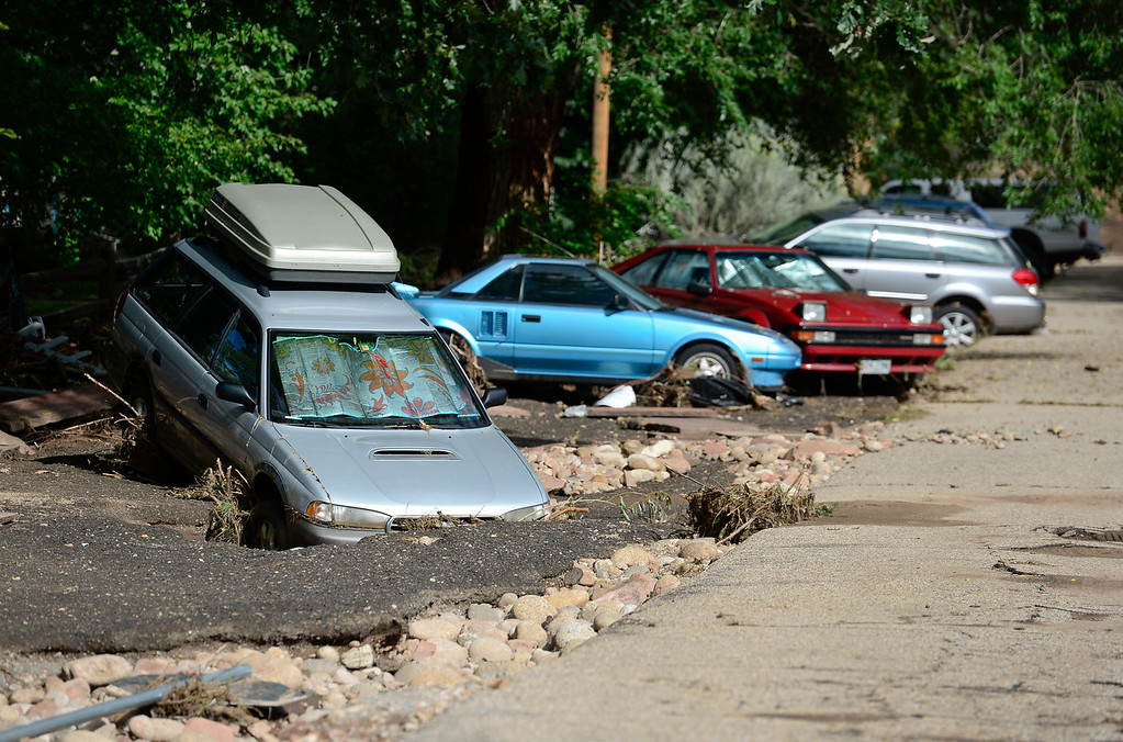 Description of . A line of cars damaged by flood water is seen, Monday, Sept. 16, 2013, in Lyons.