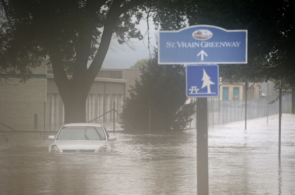 Description of . A car floats in the flood water near Third Ave and Hover Street, Thursday, Sept. 12, 2013, at (Matthew Jonas/Times-Call)