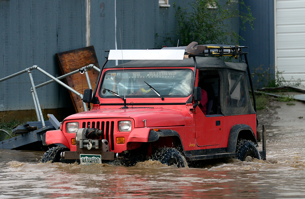 Description of . A Jeep drives through water at 51 S. Bowen Street Saturday morning, Sept. 14, 2013. (Lewis Geyer/Times-Call)