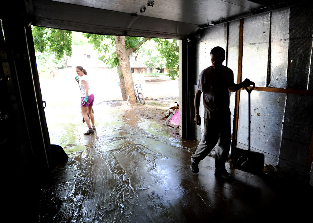 Description of . Stefani Anderson, left, and Mark Swanson clean mud out of the garage of their home on Lefthand Drive in Longmont, Colorado on September 14, 2013.
