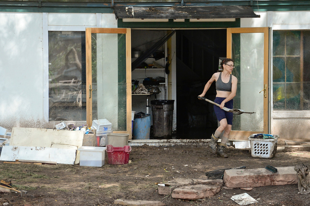 Description of . Cynthia Cappel, of Lyons, shovels mud and debris out of the basement of her house, Wednesday, Sept. 18, 2013, near the St. Vrain River.