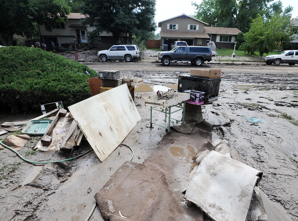 Description of . The flood damaged belongings of this family are taken outside of this mud filled home on Lefthand Drive in Longmont, Colorado on September 14, 2013.
