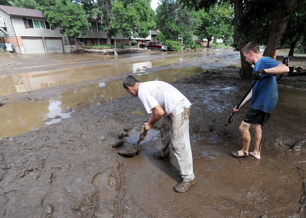 Description of . Longmont Flood Damage Day 3 274.JPG Mark Swanson, left, and Gabe Anderson, shovel out the mud from this home on Lefthand Drive in Longmont, Colorado, on September 14, 2013.