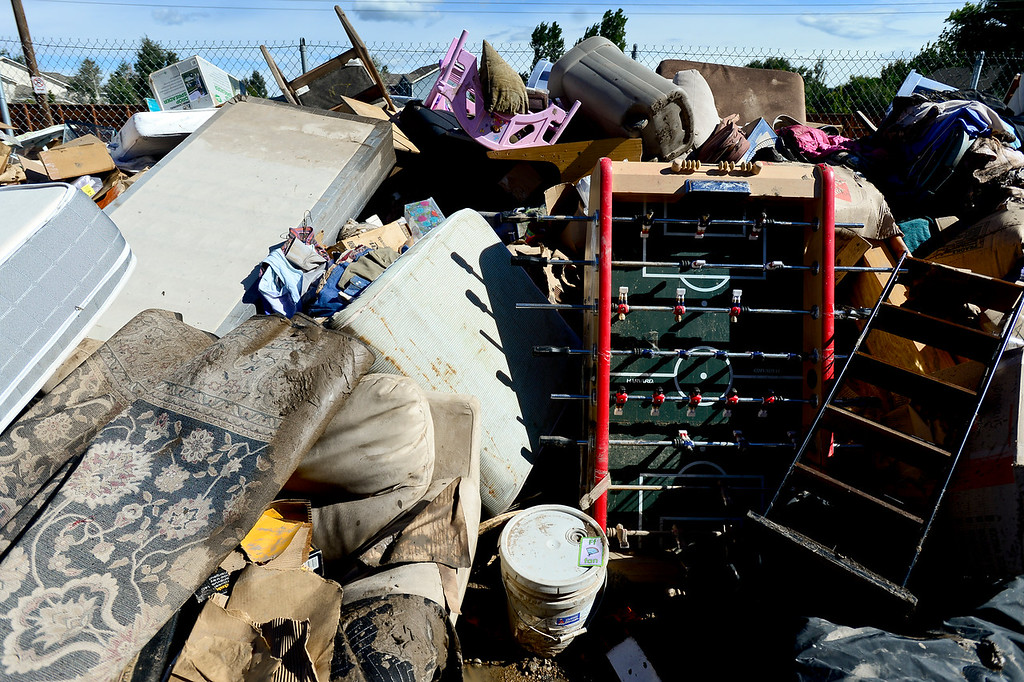Description of . A huge pile of flood damaged belongings are seen stacked outside storage units, Monday, Sept. 23, 2013, at Storage West Self Storage in Longmont.