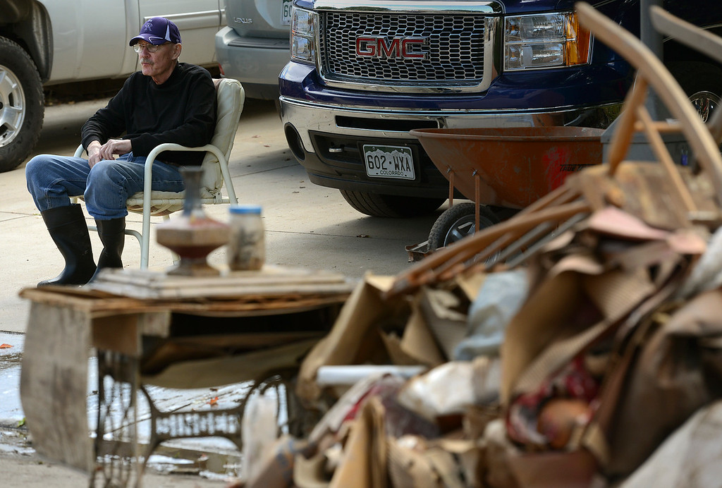 "Description of . As his basement is being cleaned out by volunteers, homeowner Larry Doescher sits in his driveway along Twin Peaks Circle in The Greens neighborhood Thursday, Sept. 19, 2013. ""It\'s like your life is being thrown away,\"" Doescher said. (Lewis Geyer/Times-Call)"