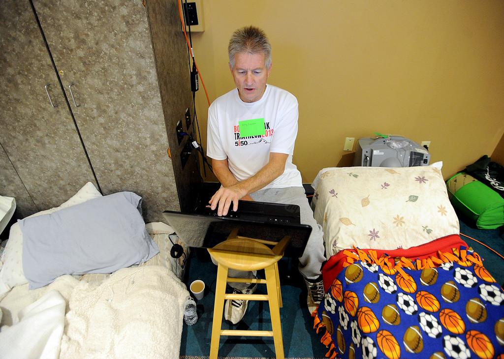 Description of . Gary Peterson, of Lyons, uses his computer to check the conditions around his home. He is staying at the LifeBridge Church in Longmont, Colorado on September 15, 2013. Cliff Grassmick / September 15, 2013