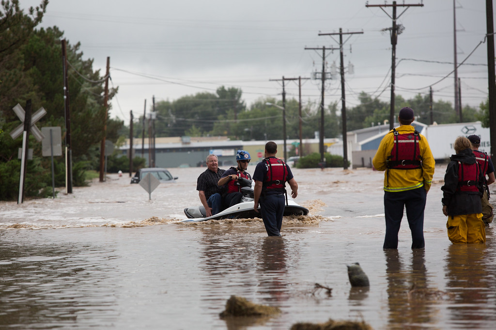 Description of . Rescue workers evacuate people from area businesses by jet ski as as the St. Vrain river floods after days of torrential rains, on Thursday Sept. 12, 2013 in Longmont, Colo.