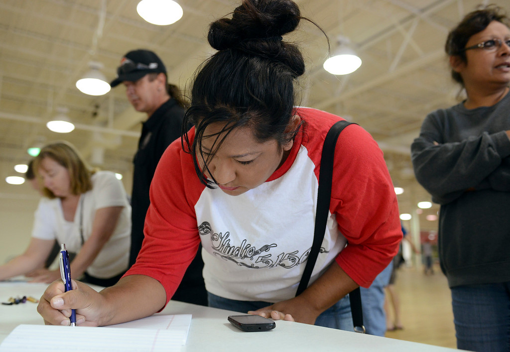 Description of . Victoria Encinia puts her contact information on a list at Longmont\'s Disaster Recovery Center at Twin Peaks Mall Monday, Sept. 16, 2013. (Lewis Geyer/Times-Call)