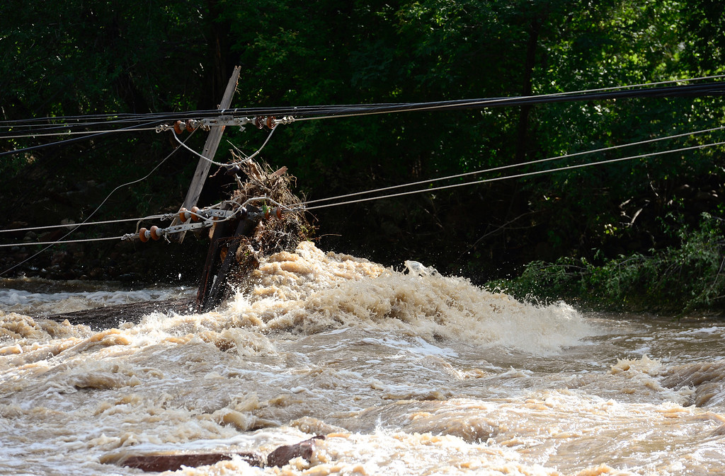 Description of . A power pole and lines are seen in the St. Vrain River, Monday, Sept. 16, 2013, off Highway 66 in Lyons. Power is out for much of Lyons and the surrounding communities.