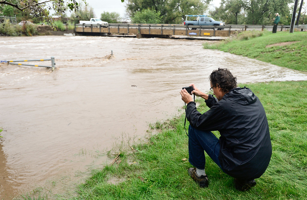 Description of . Gerardo Brucker, of Longmont, takes photos of St. Vrain River at Izaak Walton Park in Longmont, Thursday, Sept. 12, 2013, at (Matthew Jonas/Times-Call)