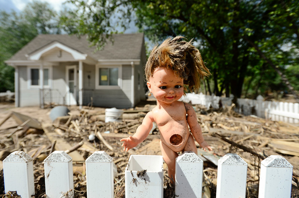 Description of . A doll is seen stuck in a white-picket-fence near a home that is surrounded by mud and debris, Wednesday, Sept. 18, 2013, in Lyons. 