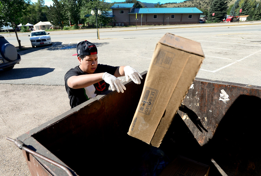 Description of . Smokin\' Dave\'s BBQ and Taphouse bus boy and prep cook Jesus Montes, 15, throws out spoiled meat, Wednesday, Sept. 18, 2013, in Lyons.
