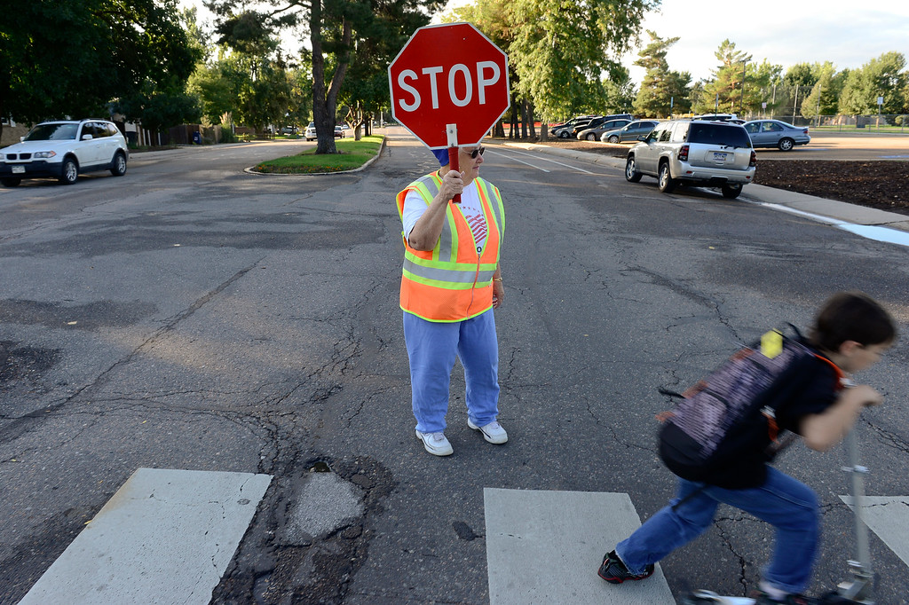 Description of . Janice Schumacher stops traffic on South Pratt Parkway for Burlington Elementary students Thursday morning, Sept. 19, 2013, the first day school is in session since the flood. (Lewis Geyer/Times-Call) TO VIEW A VIDEO VISIT WWW.TIMESCALL.COM