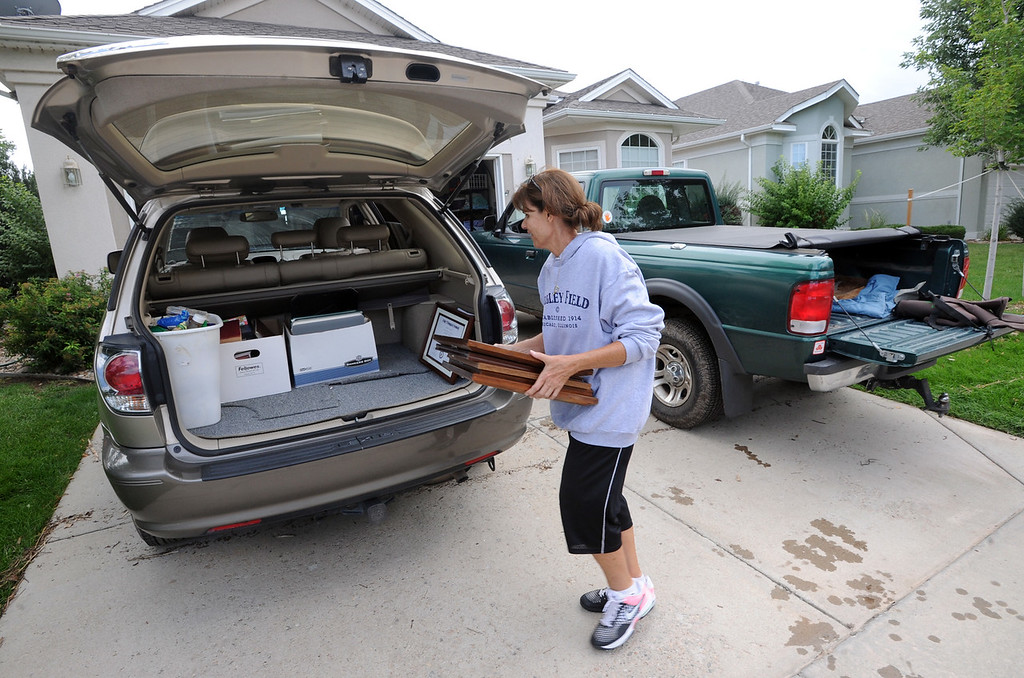 Description of . Longmont Flood Damage Day 3 478.JPG Judy Laursen helps a neighbor load belongings in a car in the Champion Neighborhood in Longmont, Colorado on September 14, 2013. Residents were allowed in for an hour to get belongings on Saturday.