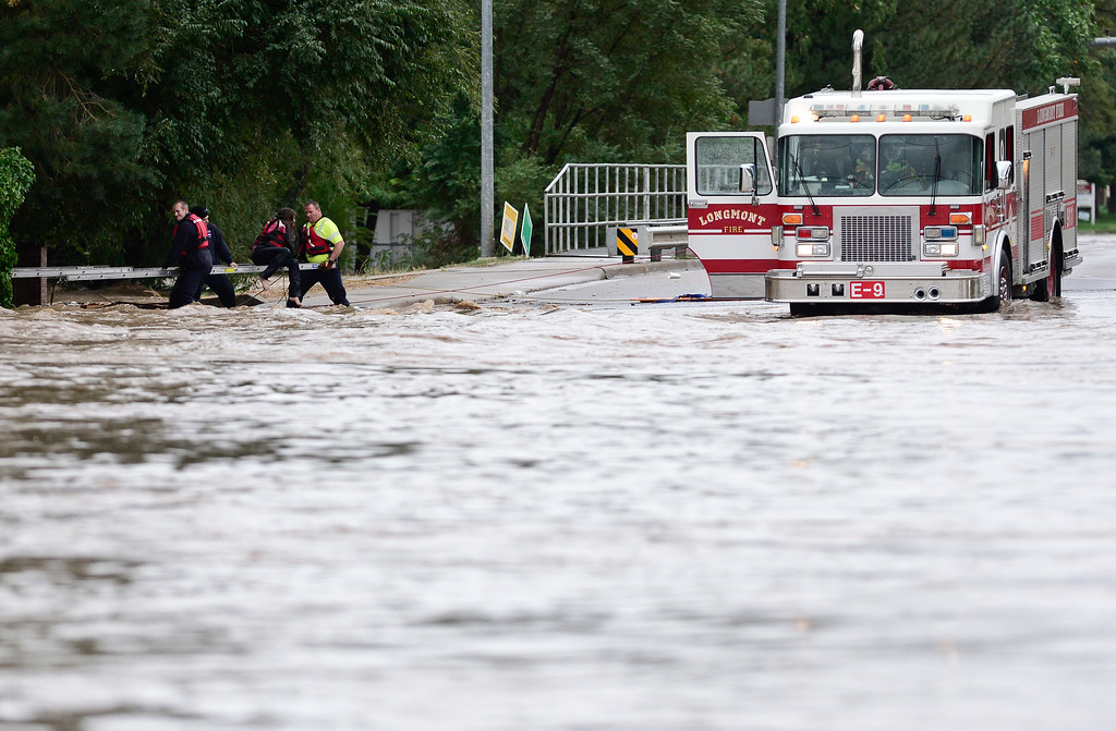 Description of . Longmont Fire Department firefighters work to hold a ladder to rescue a woman who was stranded in high water near Pratt Street and Boston Avenue, Thursday, Sept. 12, 2013, in Longmont.