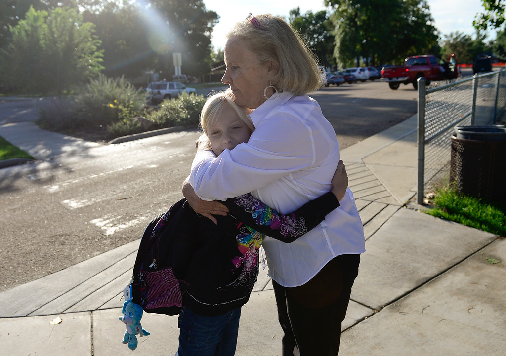 Description of . Principal Janis Hughes hugs third grader Evelynn Marchand on the first day back to school at Burlington Elementary Thursday morning, Sept. 19, 2013. Burlington is running on generator power. (Lewis Geyer/Times-Call) TO VIEW A VIDEO VISIT WWW.TIMESCALL.COM
