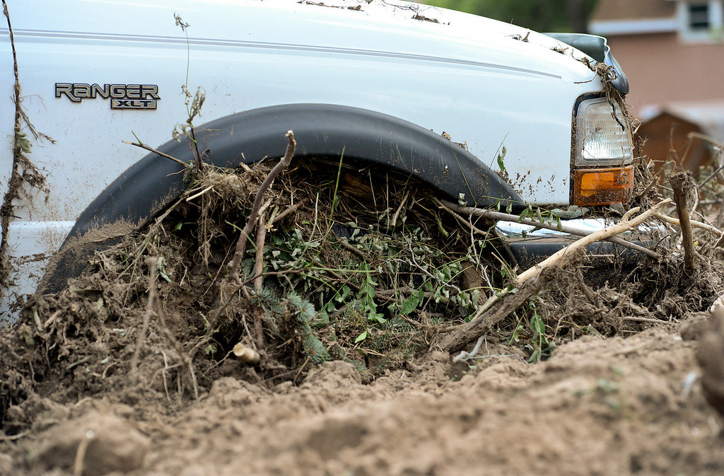 Description of . Mud and debris fills the wheel well of a pickup truck, Wednesday, Sept. 18, 2013, in Lyons.
