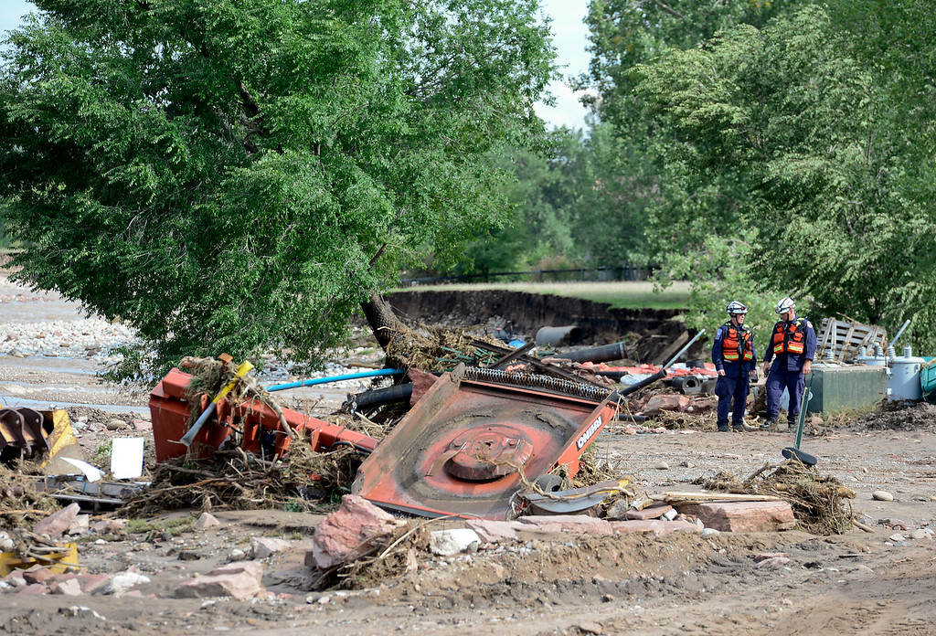 Description of . Two emergency workers are seen looking through debris near the damaged waste water treatment plant off 2nd Avenue, Monday, Sept. 16, 2013, in Lyons.