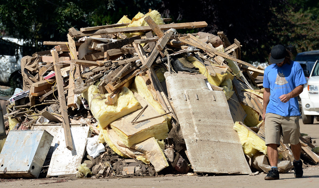 Description of . Volunteer Tom Suliman walks past a pile of garbage on Columbia Drive in The Greens neighborhood Thursday, Sept. 19, 2013. (Lewis Geyer/Times-Call)