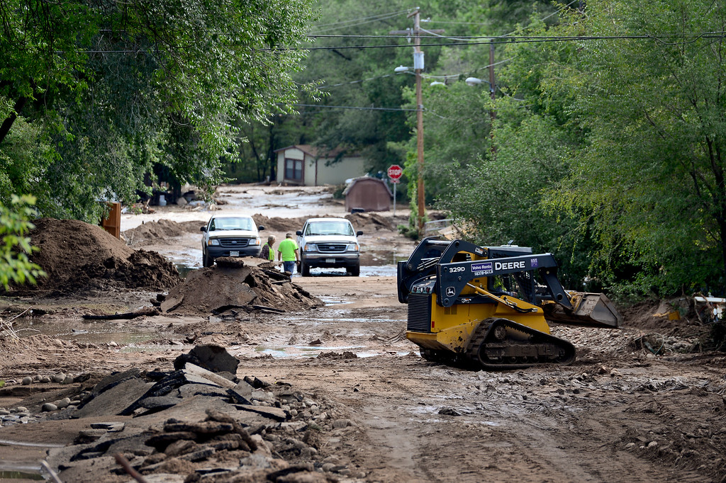 Description of . Mud and debris is cleared from Park Street, Monday, Sept. 16, 2013, in Lyons.