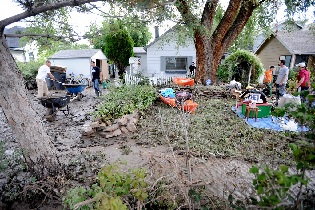 Description of . Friends and family work to clean up the flood damage at their home at 1st Ave. and S. Bowen, in Longmont, during the morning of September 14, 2013.