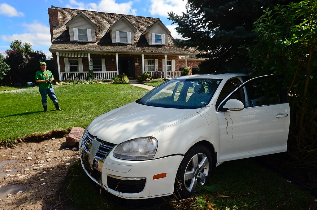 Description of . Lou Belletire, of Longmont, looks at his car which floated into his neighbors front yard on Twin Peaks Circle, Monday, Sept. 16, 2013, in Longmont.