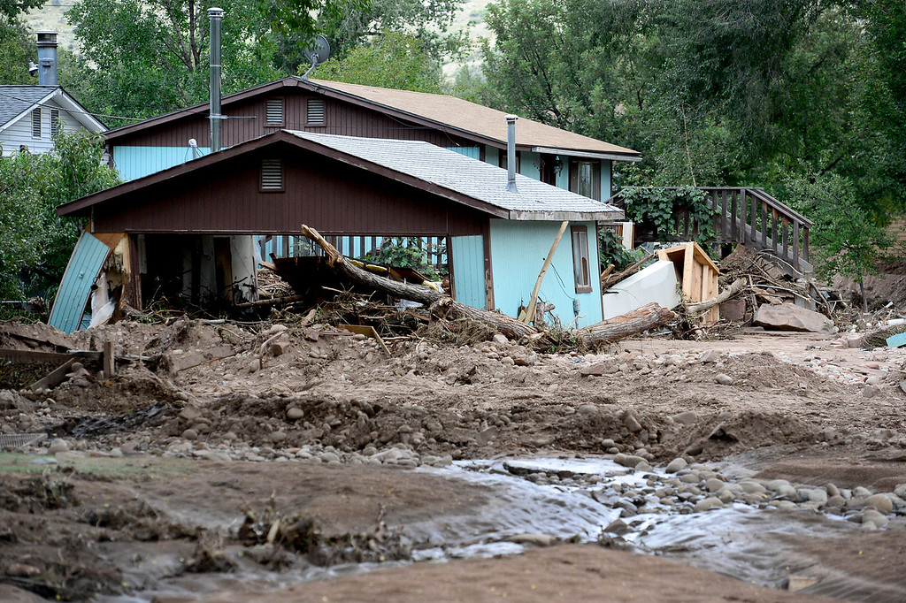 Description of . Streets filled with mud and debris and a garage that appears to be leaning is seen, Wednesday, Sept. 18, 2013, in Lyons.