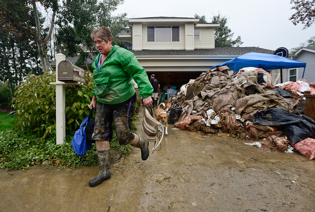Description of . Longmont resident Kristin McDonald and her dog Sakari quickly evacuate their home after a notice from the city that conditions up stream had changed, Sunday, Sept. 15, 2013, in Longmont.