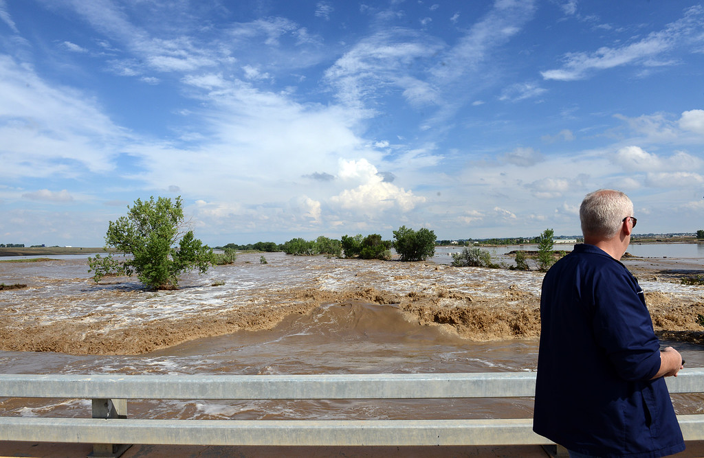 Description of . 20130913_FLOODING_LG_191.jpg Mead resident Court Stout watches the water pour through the swollen St. Vrain River at the East Frontage Road, north of Del Camino, Friday afternoon Sept. 13, 2013. (Lewis Geyer/Times-Call)