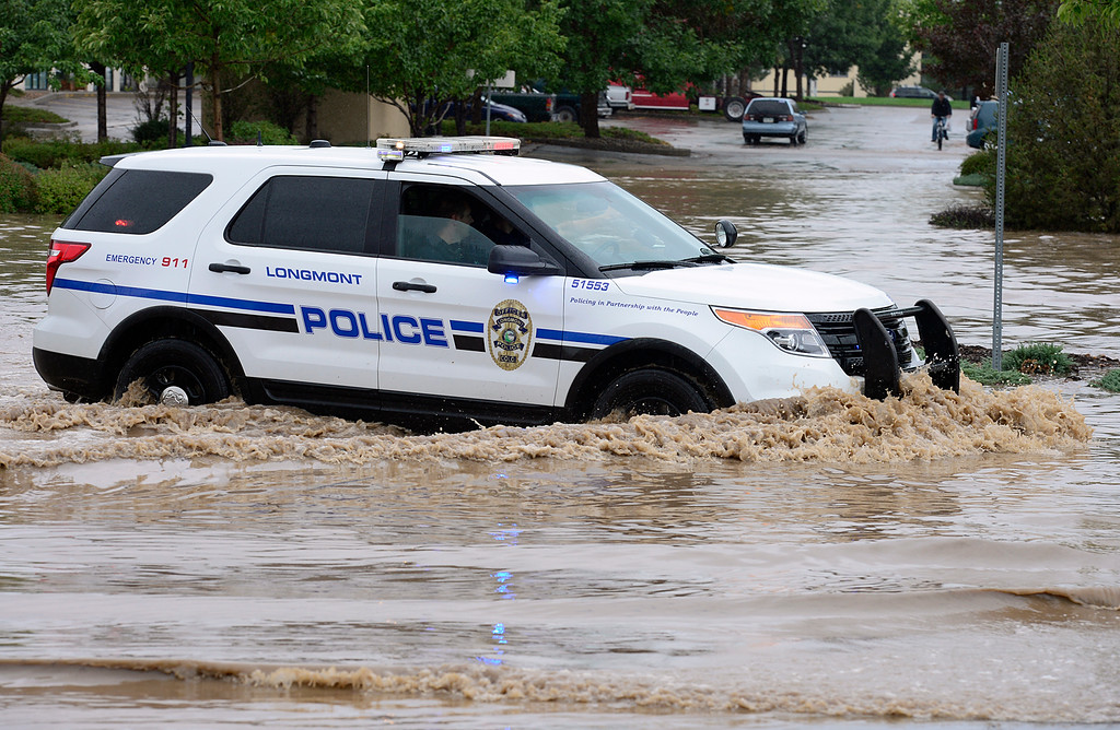 Description of . A Longmont police car drives through a flooded parking lot adjacent to a flooded Warren Avenue near South Main Street Thursday Sept. 12, 2013. (Lewis Geyer/Times-Call)