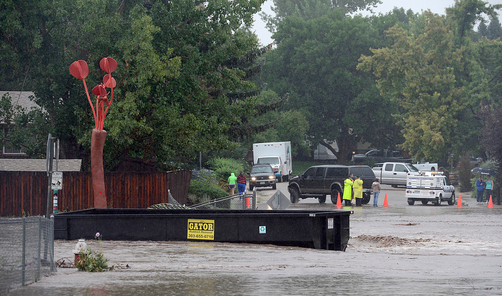 Description of . A large metal dump container that floated down the St. Vrain River sits on a flooded Missouri Avenue 10 a.m. Thursday Sept. 12, 2013. (Lewis Geyer/Times-Call)