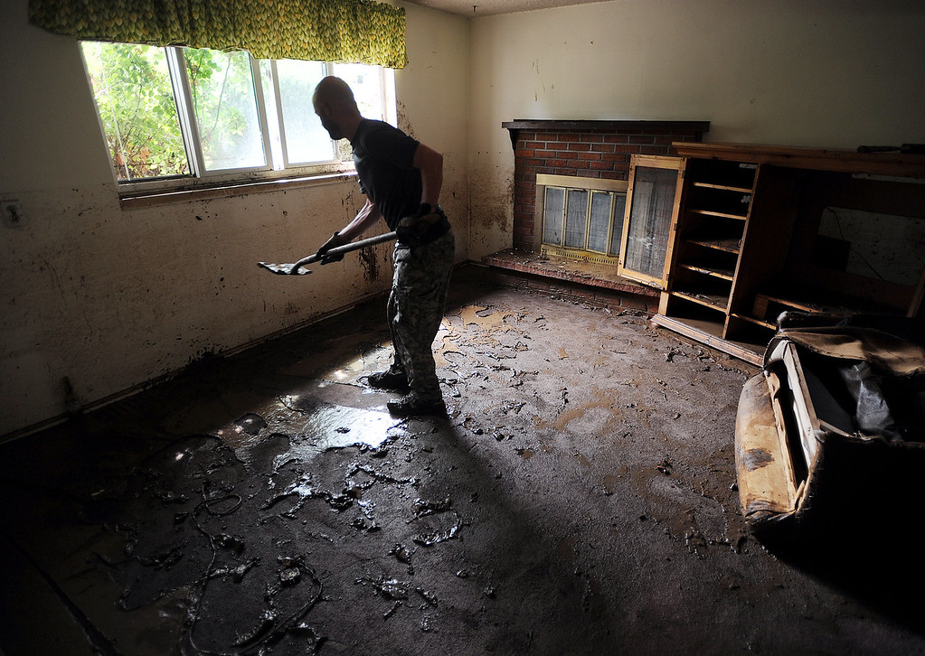Description of . Mike McDaniels shovels out mud from the basement of a friend\'s house on Lefthand Drive in Longmont Colorado, on September 14, 2013.