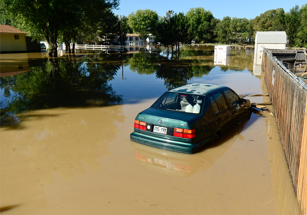 Description of . A flooded car sits near the entrance to River Valley Village mobile home park, Tuesday, Sept. 17, 2013, in Del Camino.