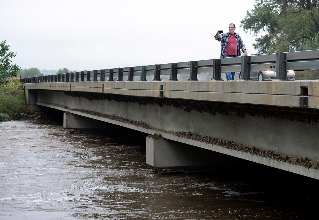 Description of . Russ Oberg, of Arvada, photographs a swollen Boulder Creek along Hwy. 287 Thursday morning Sept. 12, 2013. (Lewis Geyer/Times-Call)