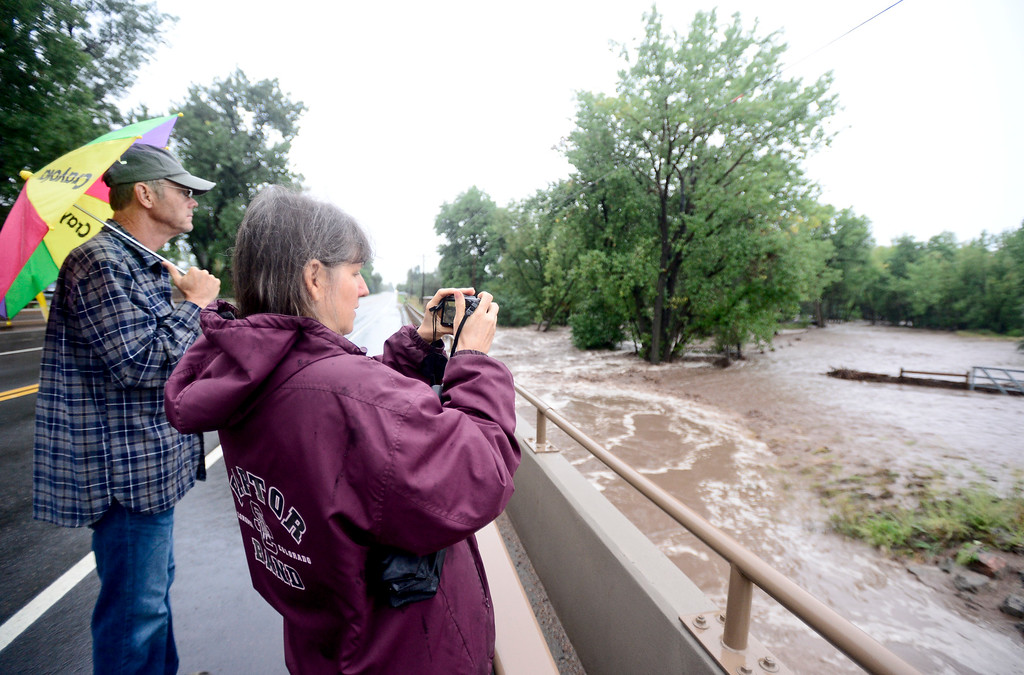 Description of . Carolyn Stefansky and Mark Stefansky watch as the Lefthand Creek floods nearby land from the bridge at North 63rd Street, Thursday, Sept. 12, 2013, near Niwot.